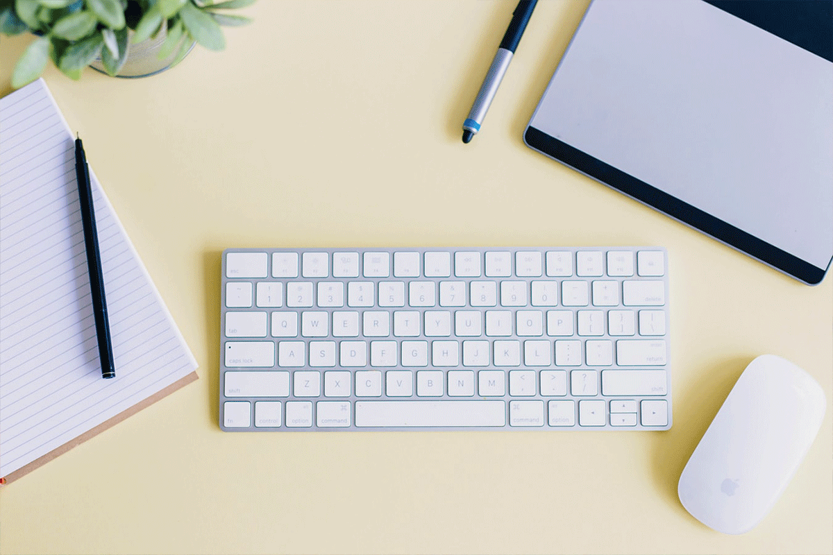 Wireless keyboard and mouse against yellow desk | Photo: Amy Hirschi via Unsplash