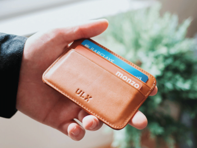 Person holding brown ULX leather wallet | Photo: Oliur via Unsplash