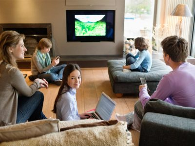 Family with electronics in living room