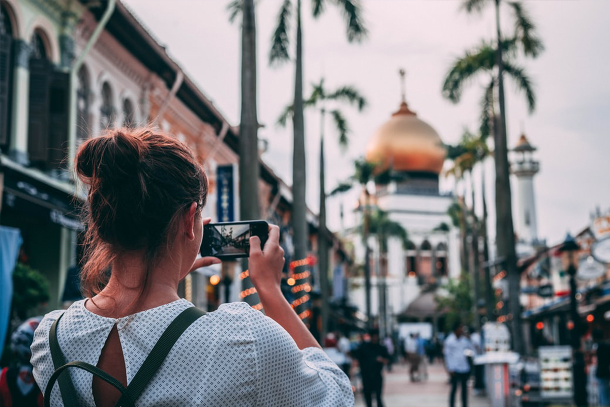 Selective focus photography of women taking photo in Singapore | Photo: Charles Postiaux via Unsplash