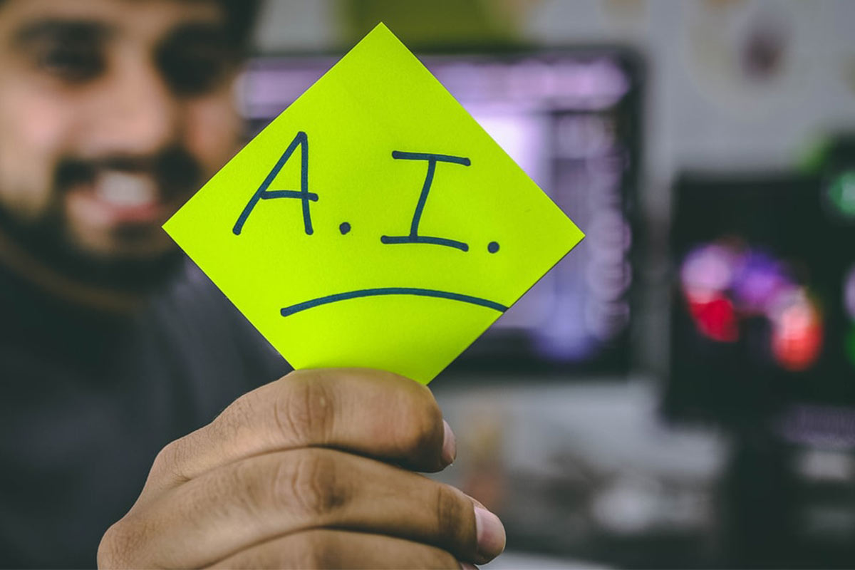 Person holding green paper with AI written on | Photo: Hitesh Choudhary via Unsplash
