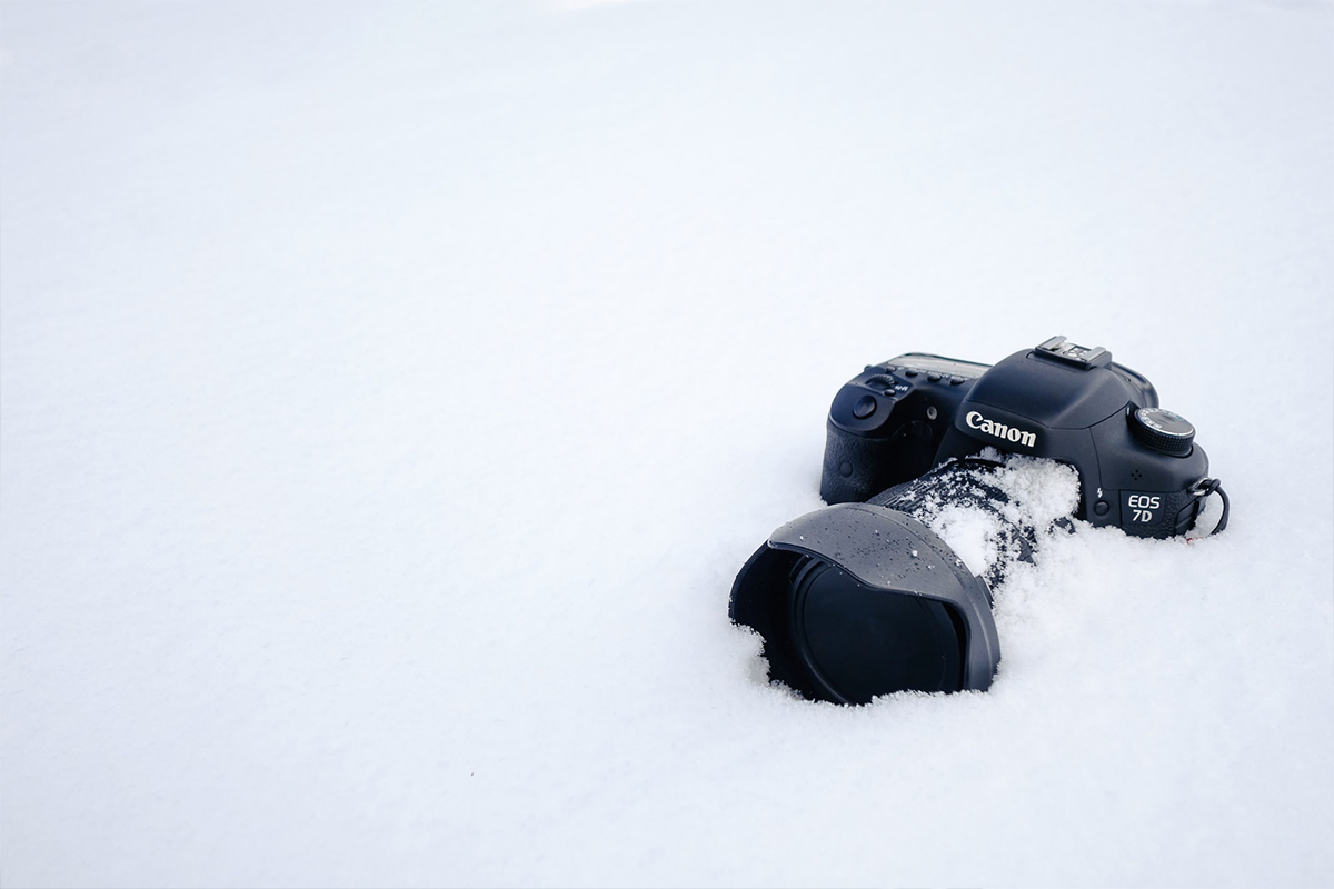 Black Canon DSLR camera on snow field | Photo: Arno Body