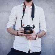 Man in white dress shirt holding Canon DSLR camera | Photo: Freestocks via Unsplash
