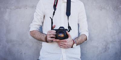 Man in white dress shirt holding Canon DSLR camera | Photo: Freestocks via Unsplash