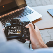 Photographer working on his DSLR camera in cafe | Photo: JESHOOTS via Unsplash