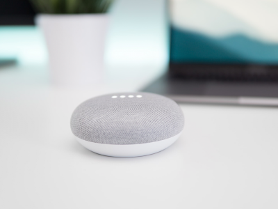 Turned on grey and white Google Home Mini speaker on white surface | Photo: Kevin Bhagat via Unsplash
