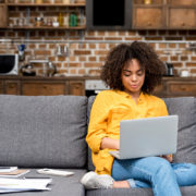 Young woman working working with laptop on couch | Photo: LightField Studios via Shutterstock