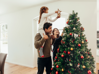 Family decorating a Christmas tree | Photo by Jacob Lund via Shutterstock