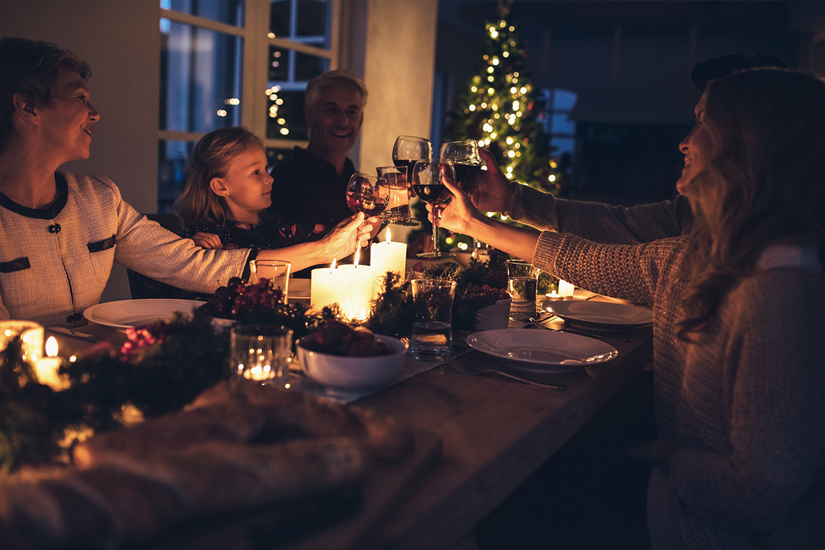 Happy extended family toasting drinks during Christmas dinner | Photo by Jacob Lund via Shutterstock