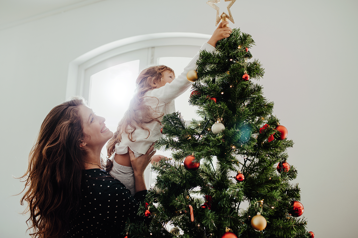 Little girl placing a star on the top of Christmas tree | Photo by Jacob Lund via Shutterstock