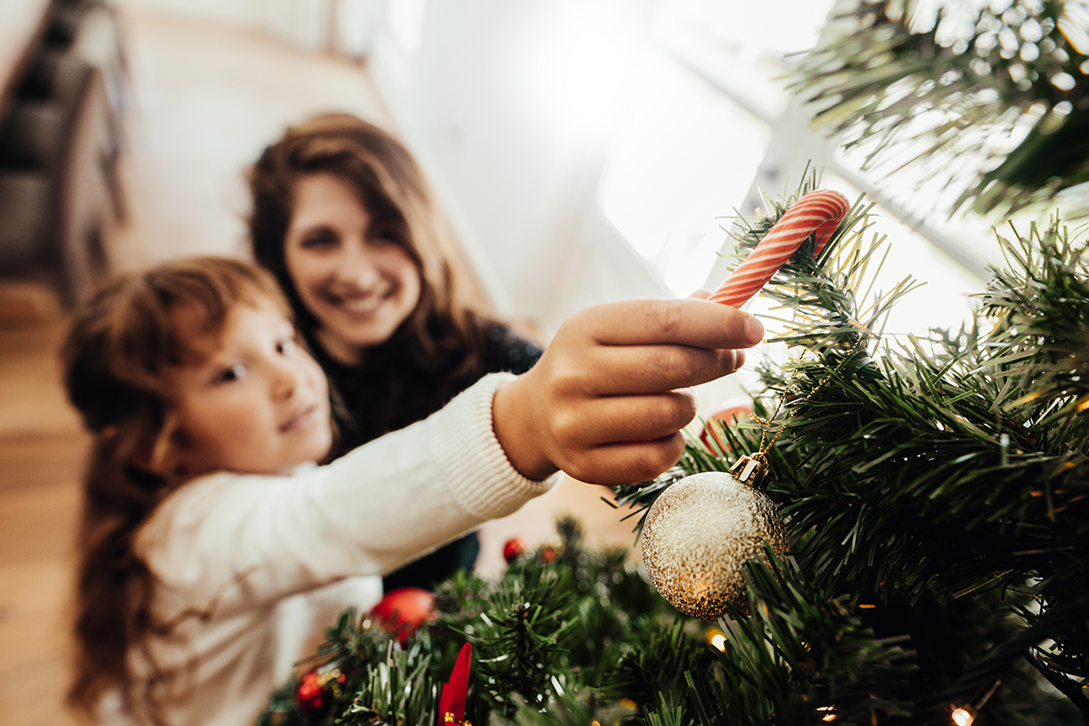Mother and daughter placing candy cane on Christmas tree | Photo by Jacob Lund via Shutterstock