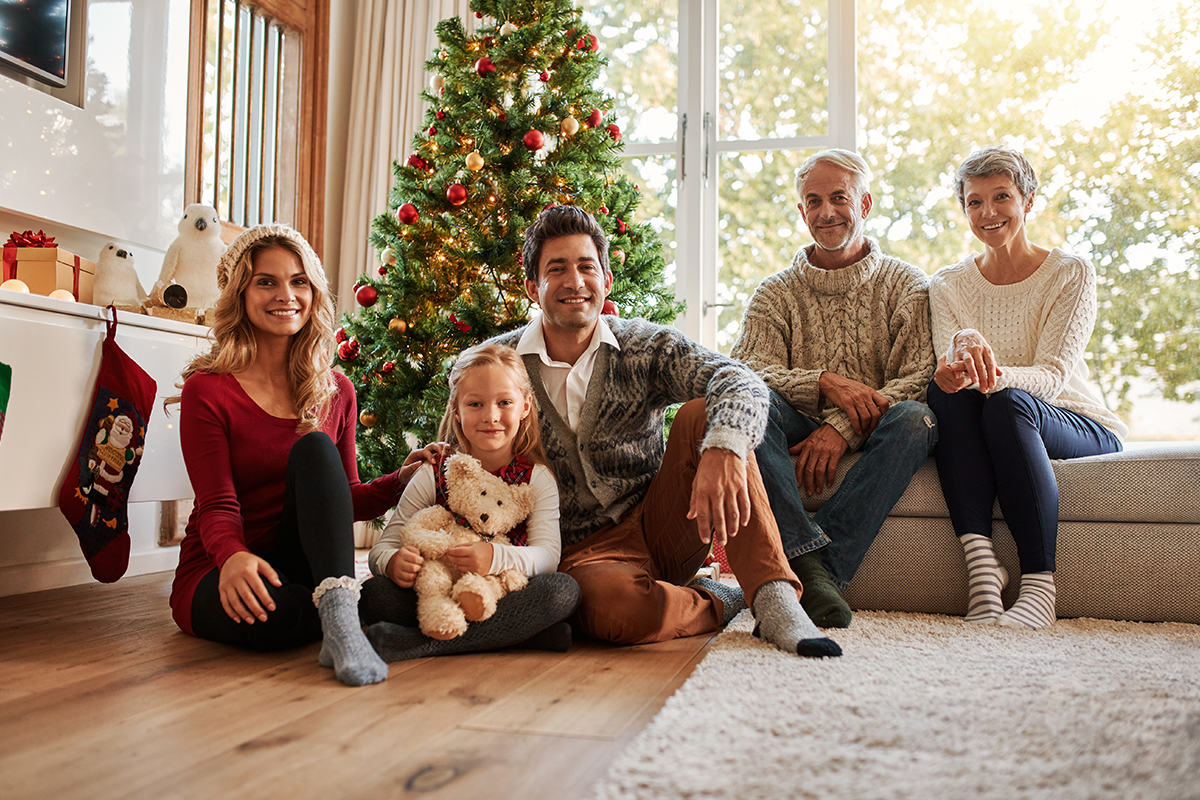 Portrait of multi generation family in front of Christmas tree | Photo by Jacob Lund via Shutterstock