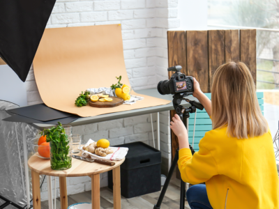 Young woman taking picture of lemons in home studio | Photo: New Africa via Shutterstock