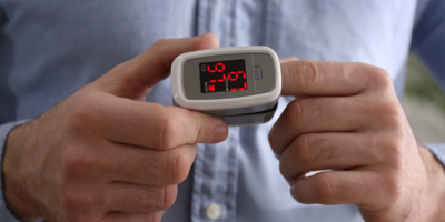 Man measuring oxygen level with fingertip pulse oximeter up-close | Photo: New Africa via Shutterstock